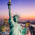 A view of the Statue of Liberty in New York at night, which can be visited via a cheap flight from Flight Centre.